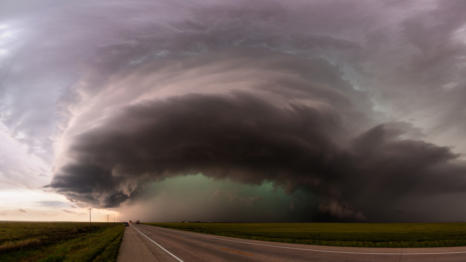 A monster supercell begins to cross highway 385 south of Lamar, Colorado. We had raced north as the rain began to hit us, and we stopped after a few miles to take in the view of this incredible storm and that stunning blue-green hailcore.