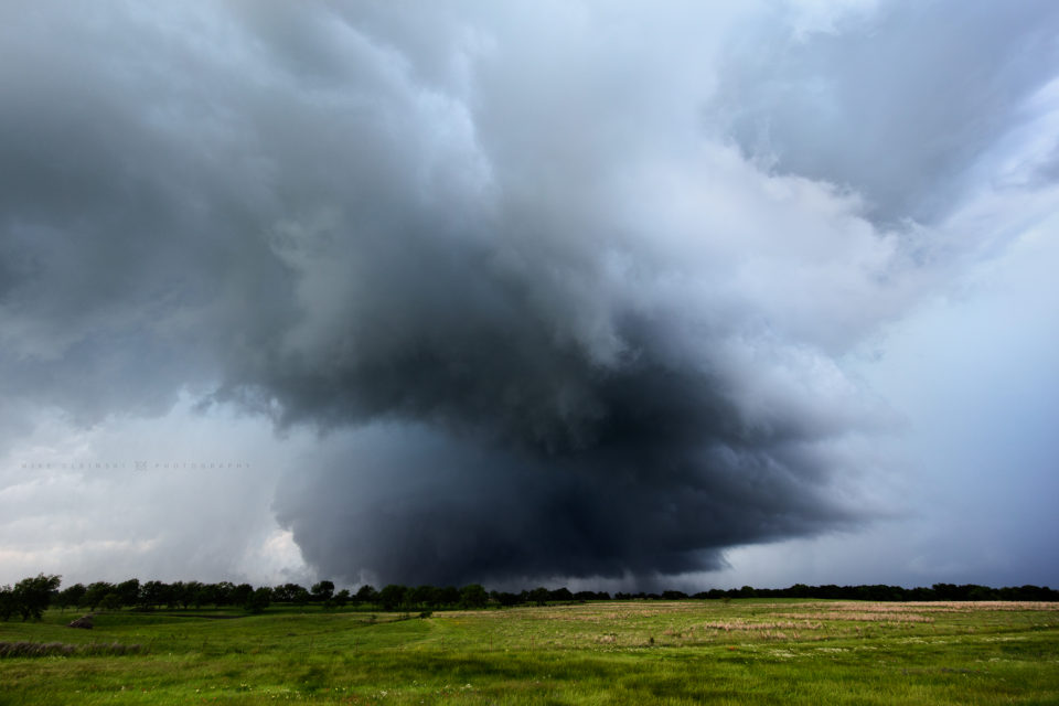 A mile-wide wedge tornado hangs out in the dark area beyond the trees as it slowly moves towards the town of Sulphur, Oklahoma.
