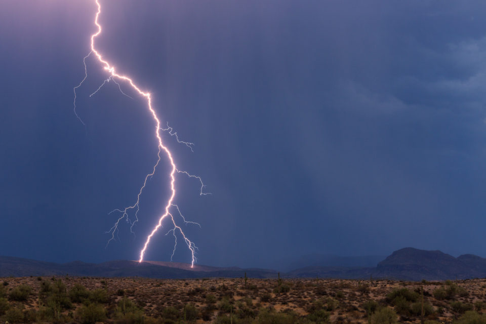 A lightning bolt lands in the Four Peaks Wilderness area northeast of Phoenix, seeming to fork into two directions at the last minute as it strikes the side of a mountain.