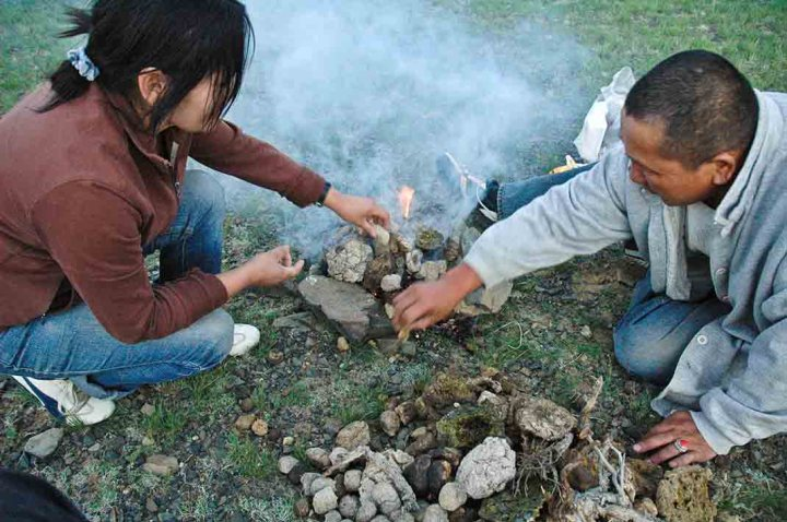 A fire is built up from dried crap around three fist-sized rocks (and kept in place with some bigger ones)