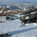Mongolia- on top of a mountain, one vehicle stuck in snow, the other with engine issues.