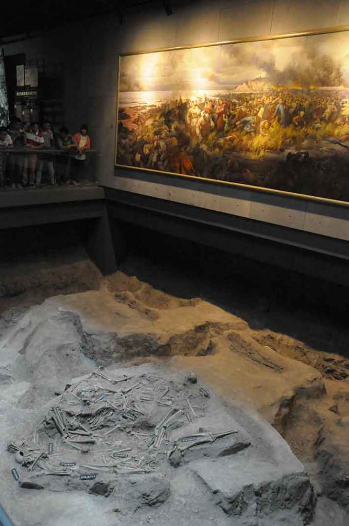 Mural of the river-side masscre, hanging above in-situ skeletons.