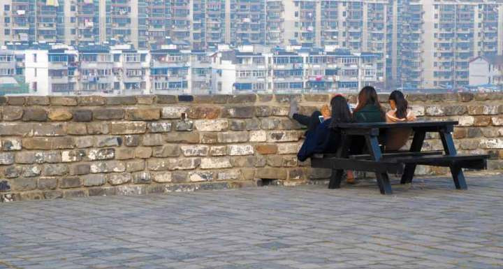 Three friends put their feet up on the Nanjing city wall.
