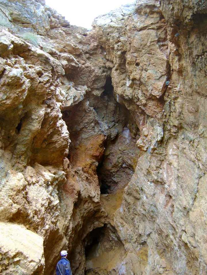 The fissure running up from the figure at the base to the top is a Roman lead-mining shaft, exposed on the edge of a recent mining pit.