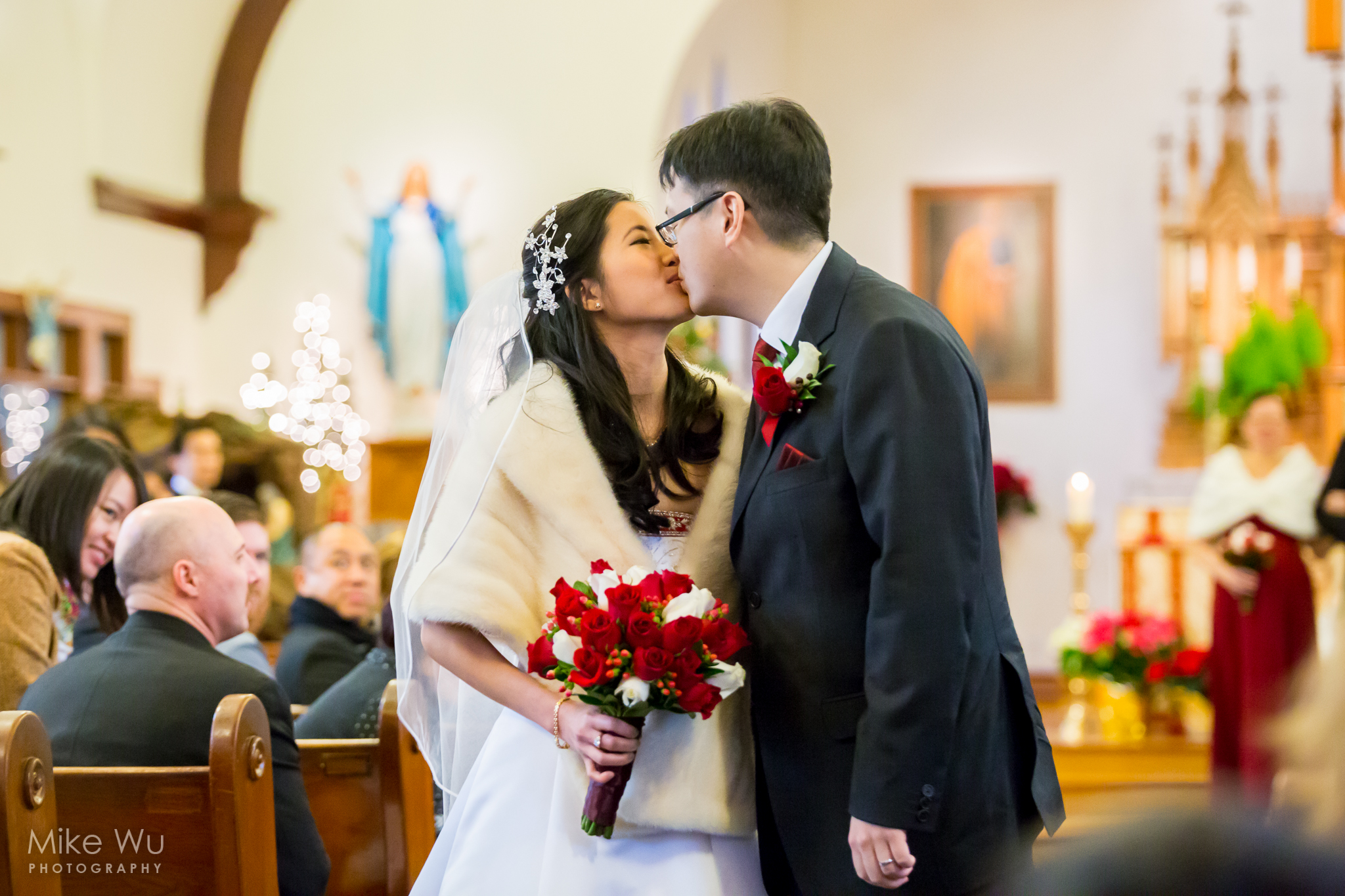 viel, fur, wedding dress, christmas wedding, bouquet, first kiss, love, vancouver, photographer, lights, crowd, attention, church, pews, indoors, winter