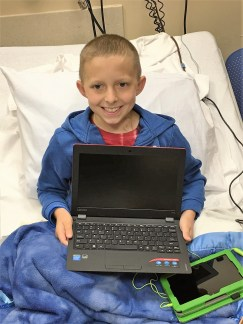 pediatric cancer patient with laptop to help cope with cancer