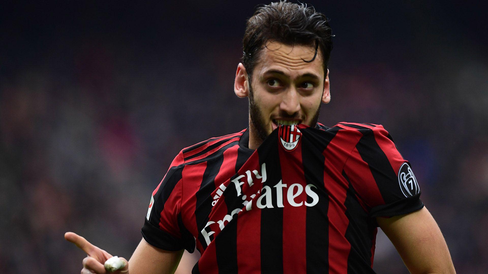 Hakan Calhanoglu morde lo stemma del Milan