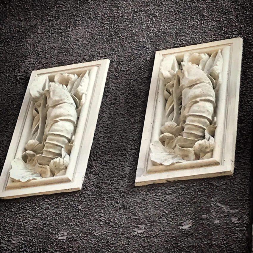 Particolare decorativo a forma di aragosta sulla facciata di Casa Frisia in zona Pagano
