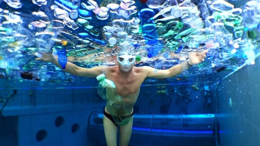 Uomo in piscina sommerso di bottiglie di plastica simula quello che accadrà al mare e a oceani se non cambiamo abitudini