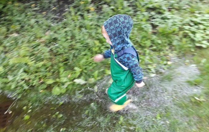 Die Regentipps - Kind rennt mit Regensachen durch große Regenpfütze