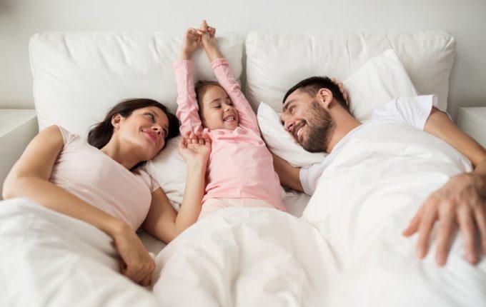 Eltern kuscheln mit Kind im Bett
