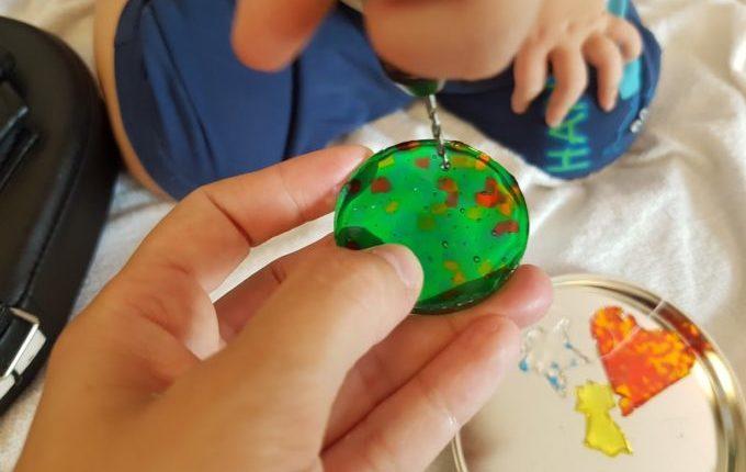 Kind bohrt mit Handbohrer Loch in Schmelzgranulat Anhänger