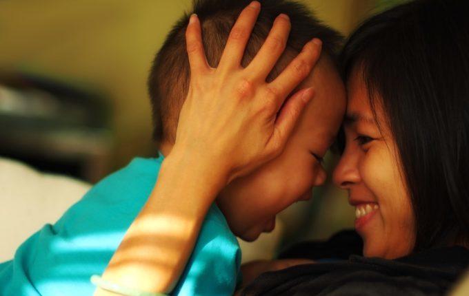 Kind und Mama kuscheln und lachen