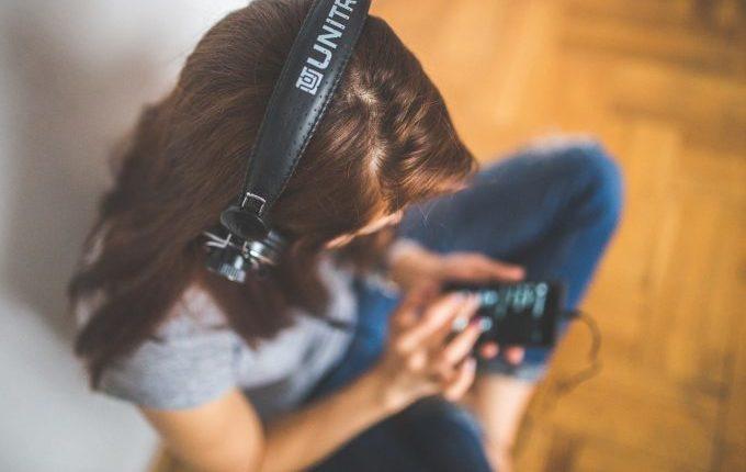 Frau hört etwas über Kopfhörer