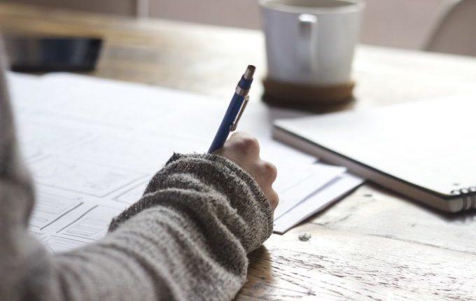 Person schreibt etwas auf ein Blatt Papier