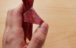 Daumen faltet spitze Nase vom Origami Osterhasen nach innen