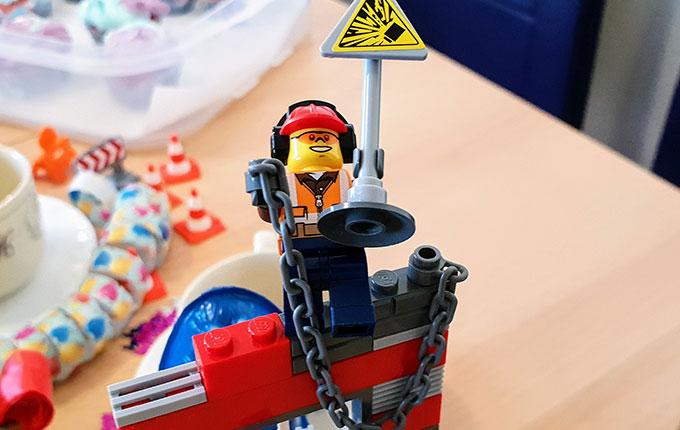 Legomännchen Bauarbeiter mit Warnschild auf der Baustelle