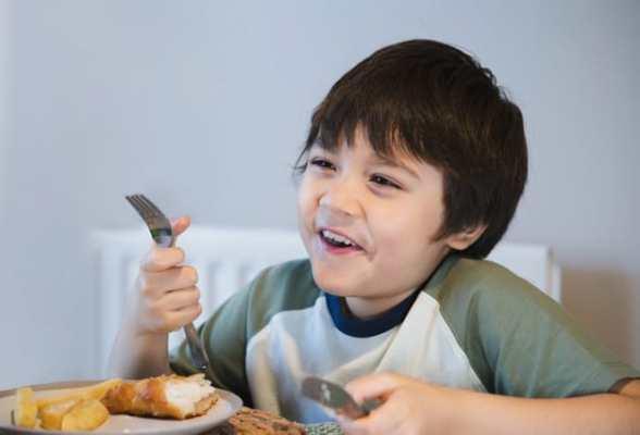 criança comendo peixe