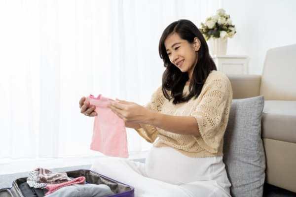 mãe organizando as roupas do bebê