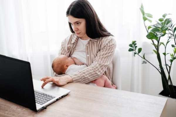 mãe usando notebook e amamentando bebê