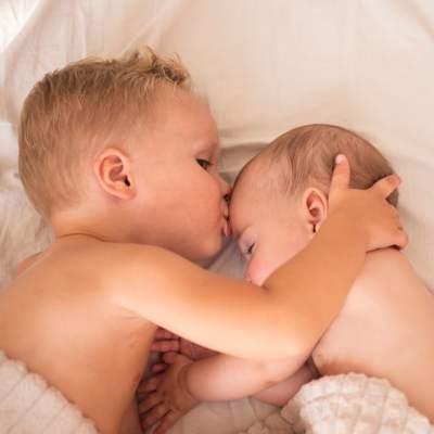 bebê dormindo e irmão beijando