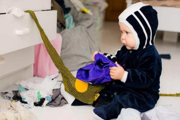 bebê mexendo nas roupas da gaveta
