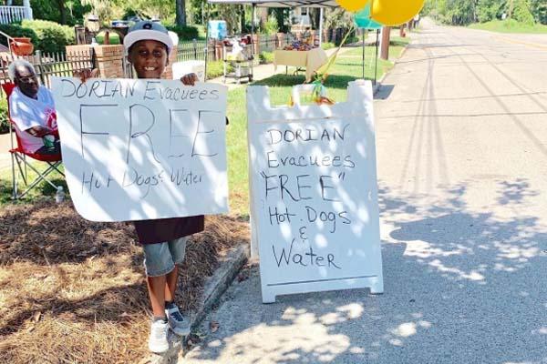 """Jermaine Bell segurando placas que dizem """"cachorro quente e água grátis"""""""