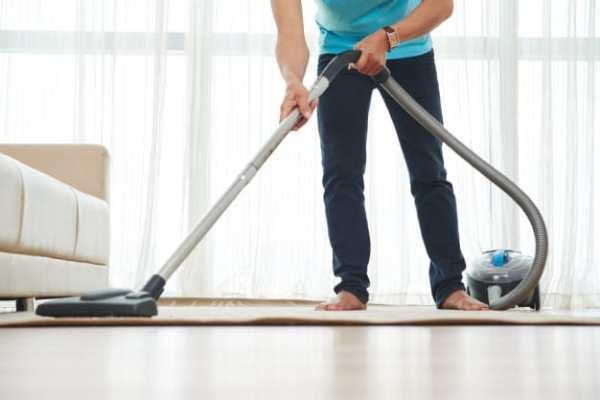 homem aspirando o tapete da sala
