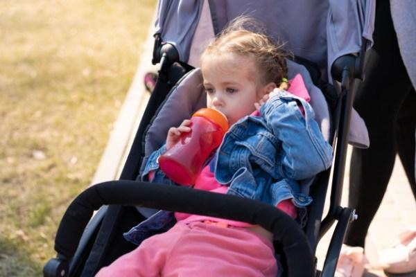 menina no carrinho tomando mamadeiras