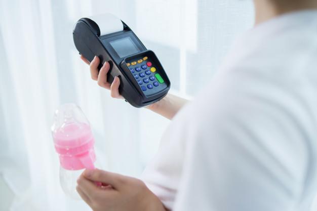 grávida com uma maquininha de cartão de crédito e uma mamadeira