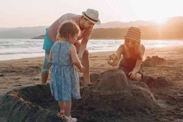 familia fazendo castelo de areia na praia
