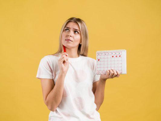 mulher com calendário marcando período fértil menstruação
