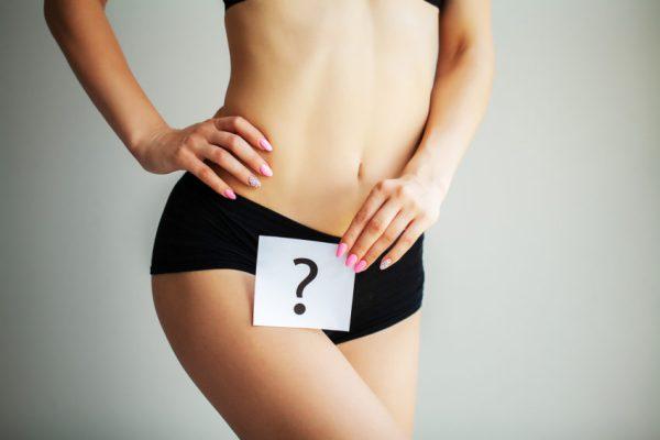mulher com placa de interrogação menstruação não desce