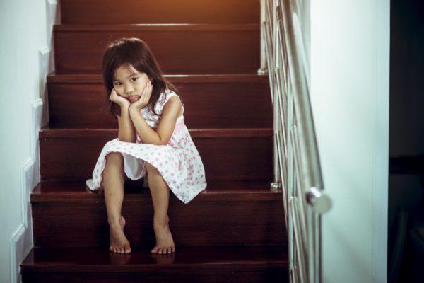 Criança triste sentada na escada com depressão infantil