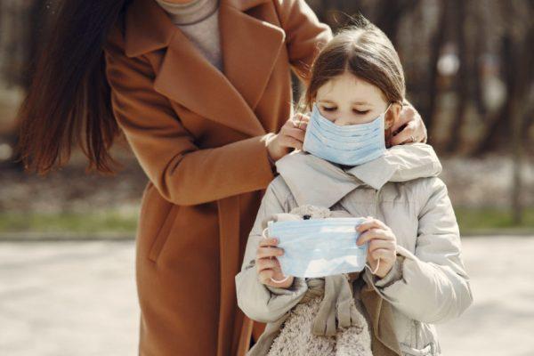mãe colocando máscara em criança para proteger de coronavírus