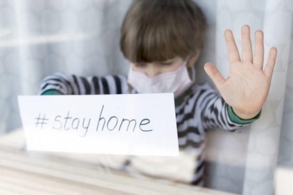 """Menino com máscara de proteção devido a coronavírus com placa escrito """"fique em casa"""" na janela de casa"""