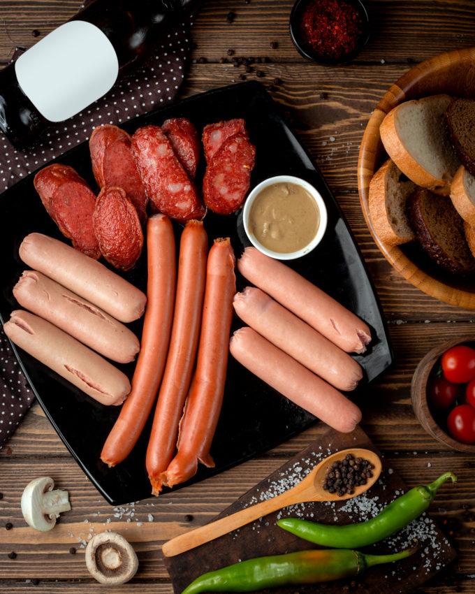 Diferentes tipos de salsichas em chapa com molho de mostarda