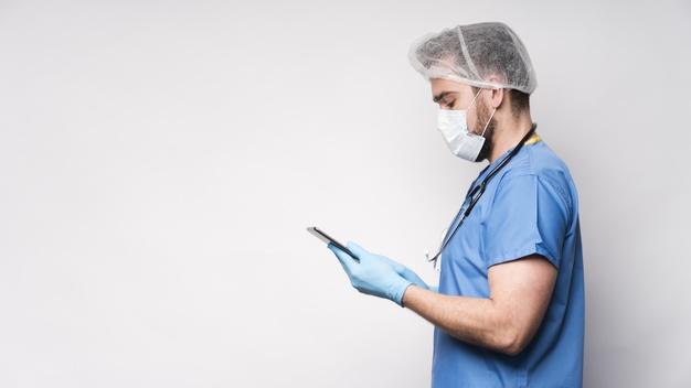 Enfermeiro de mascara olhando o celular
