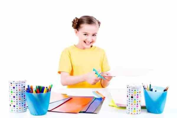 criança de 5 anos cortando papel