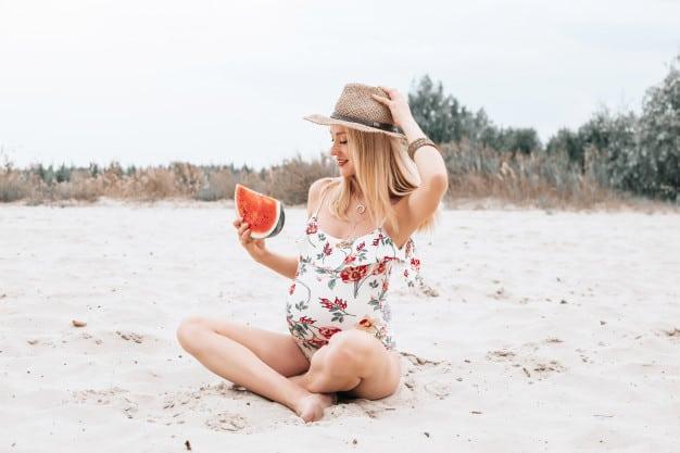 Mulher gravida com melancia na mão