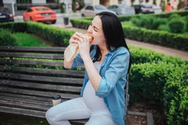 Mulher grávida comendo sanduíche
