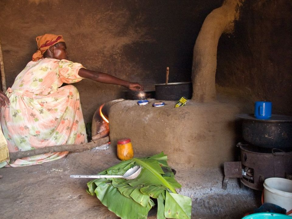 A lady cooking on a fuel efficient stove and using banana leaf as a plate.