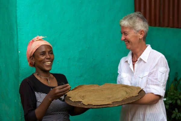 Two people holding up freshly cooked Injera, Ethiopia.