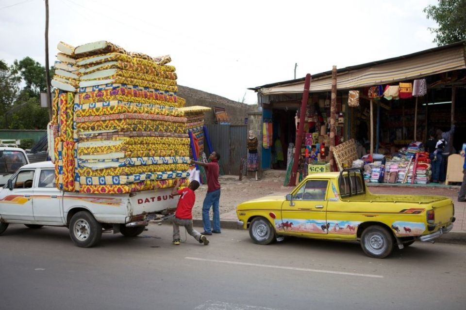 A street view of mattresses piled high on the back of a pickup vehicle, Ethiopia.