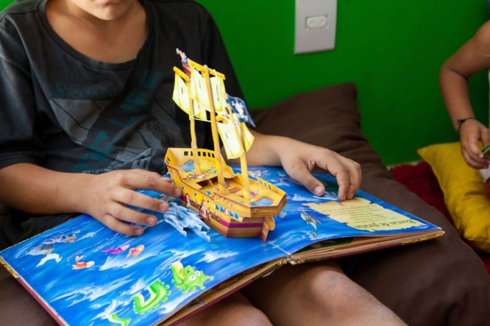 A young boy reading a pop up book