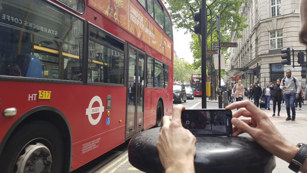 smartphone filmmaking course. A person films a London bus using a mobile phone