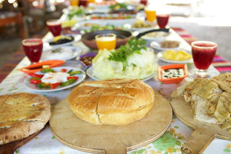 A table laden with bread and cheese and drinks ready for breakfast in Turkey.