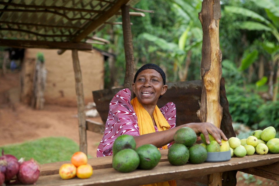 A woman selling avocados outside her house in Uganda.