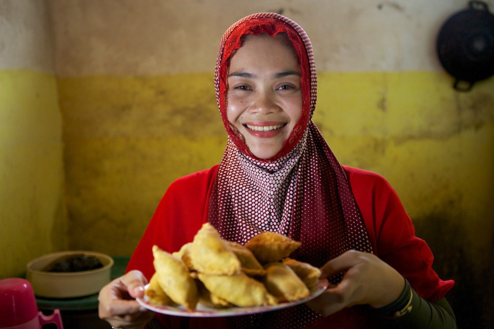 a woman smiling and holding home baked goods in Indonesia.