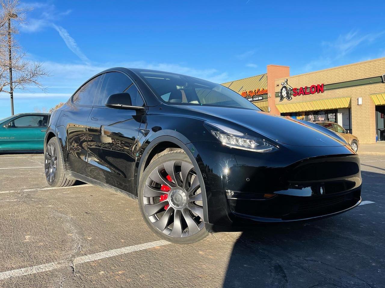 black Tesla Model Y 2 front windows tinted front side view